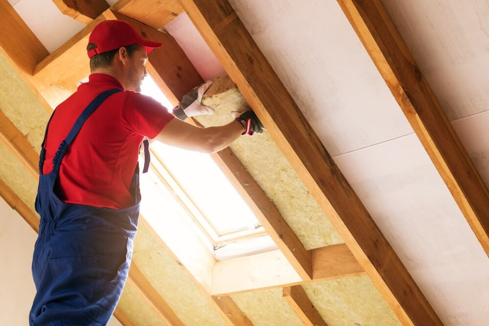 A man installing insulation in the roof of an attic